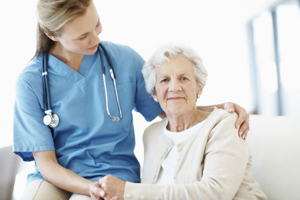 Elderly female patient holds her doctor's hand for reassurance
